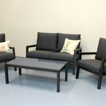 Dark grey aluminium outdoor coffee table and chairs with cushions.